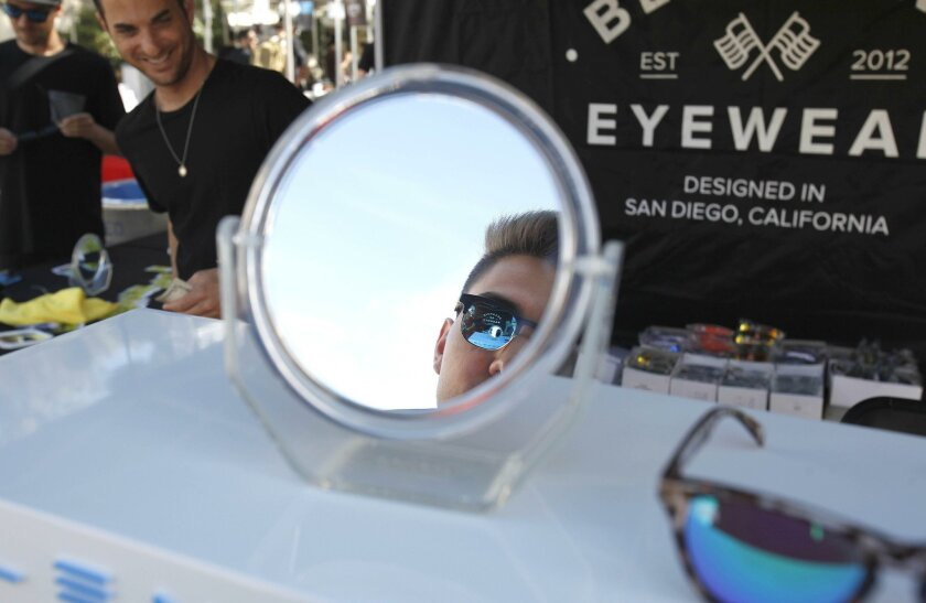 Dennis Davidoff, an exchange student from Germany, tries out different sunglasses at the Blenders Eyewear table. The company was started by Blake Jensen and Chase Fisher, both SDSU graduates.