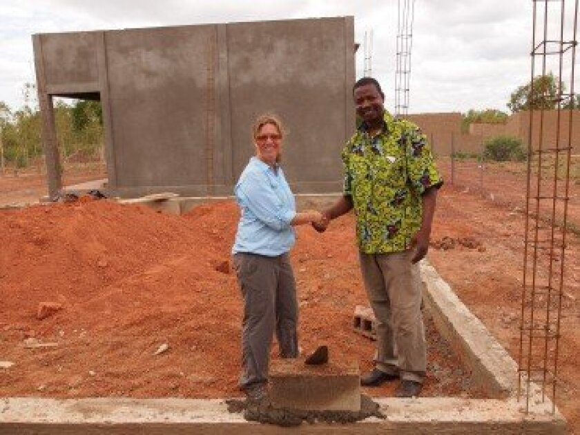 Agnes Barrelet placing the first handmade brick for the second classroom with Jean Christophe Roamba, president of Bi-Songo. Courtesy photo