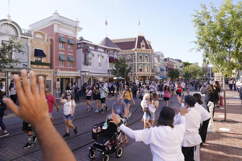 FILE - In this April 30, 2021, file photo, guests walk down Main Street USA at Disneyland in Anaheim, Calif. Los Angeles and San Francisco are reopening more businesses under California's least restrictive coronavirus safety rules, even though they have more infections than many other big counties, state data shows. (AP Photo/Jae Hong, File)