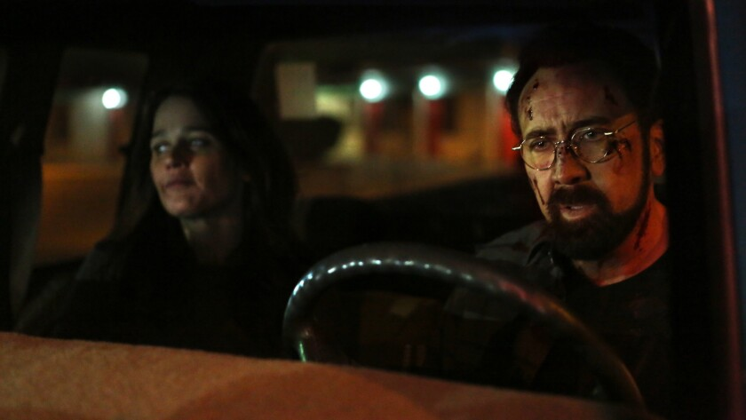 """(L-R) - Nicolas Cage as Ray and Kassia Conway as Cassie in the thriller film """"LOOKING GLASS"""" a Momen"""