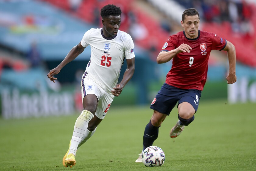 England's Bukayo Saka, left, and Czech Republic's Tomas Holes go for the ball during the Euro 2020 soccer championship group D match between Czech Republic and England, at Wembley stadium in London, Tuesday, June 22, 2021. (AP Photo/Laurence Griffiths, Pool)