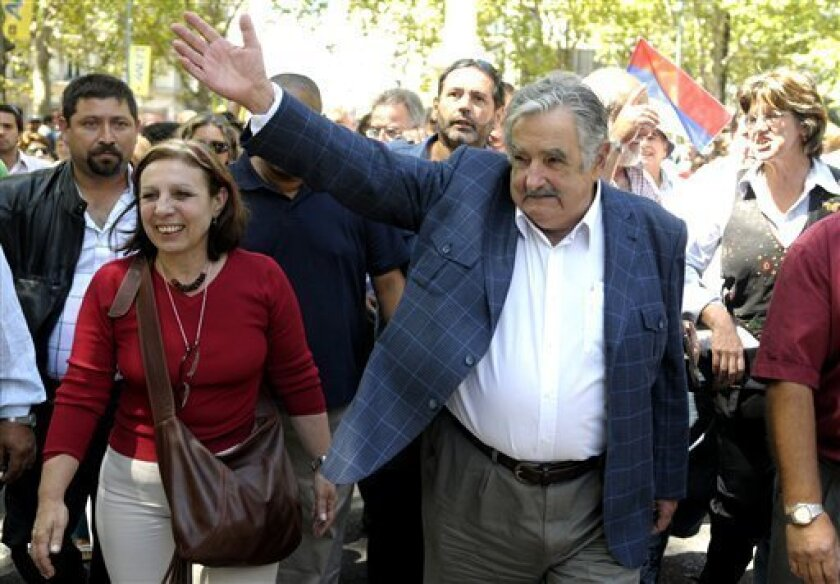 Uruguay's President-elect Jose Mujica, right, waves to supporters accompanied by Ana Olivera, left, candidate for mayor of Montevideo for Mujica's party, the Frente Amplio coalition in downtown Montevideo, Friday, Feb. 26, 2010. (AP Photo/Matilde Campodonico)