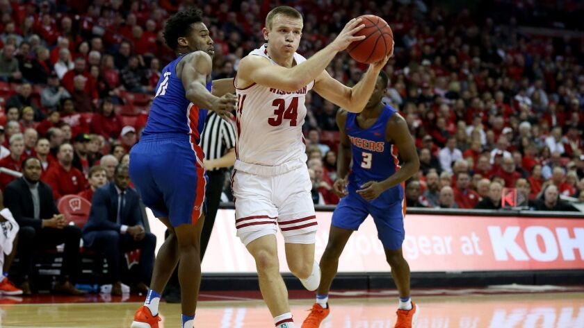 Brad Davison of the Wisconsin Badgers drives while being guarded by Jaquan Dotson of the Savannah State Tigers in the first half.