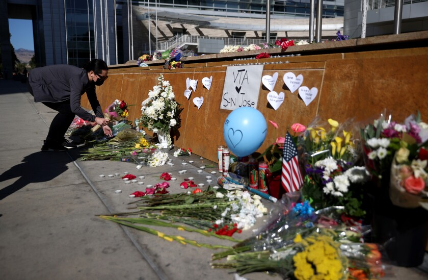 A mourner leaves flowers at a memorial for  victims of the San Jose mass shooting