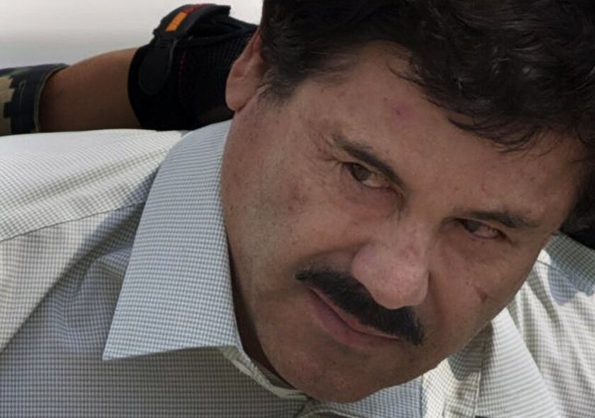 """FILE - In this Feb. 22, 2014, file photo, Joaquin """"El Chapo"""" Guzman is escorted to a helicopter in handcuffs by Mexican navy marines at a navy hanger in Mexico City. A judge in Mexico issued on Thursday, July 30, 2015, a provision warrant to detain Guzman based on an extradition request from the United States. Guzman also faces a host of Mexican charges following his July 11 escape through a tunnel from Mexico's highest-security prison. (AP Photo/Eduardo Verdugo,File)"""