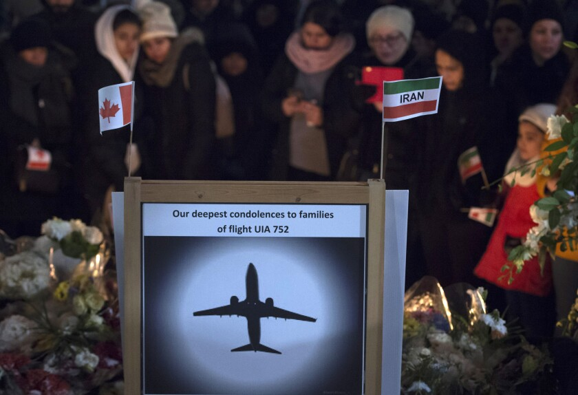 """A sign that reads """"Our deepest condolences to families of flight UIA 752"""" at a memorial."""