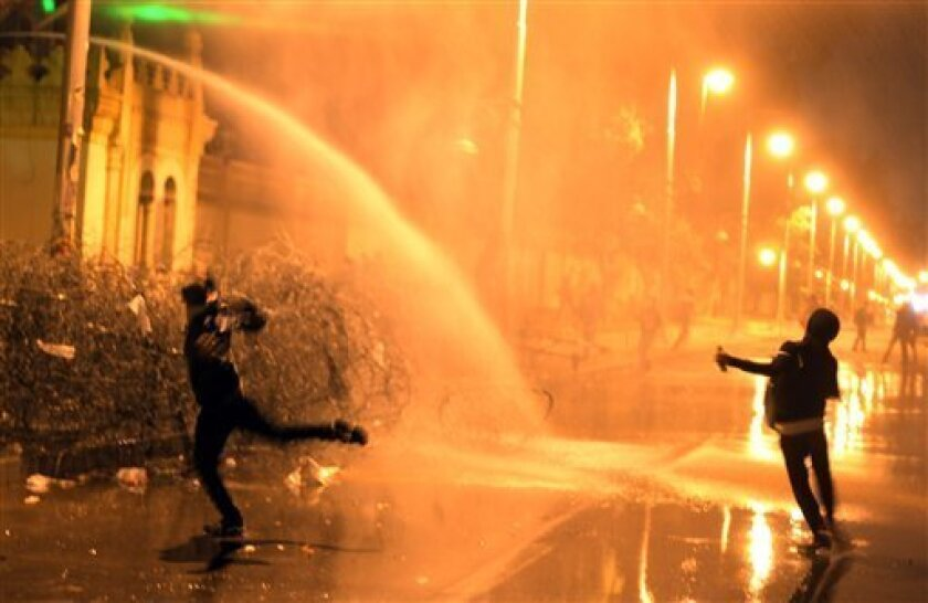 Egyptian protesters throw stones while security police open water cannons on them from inside the grounds of the presidential palace during a demonstration in Cairo, Egypt, Monday, Feb. 11, 2013. Security forces sprayed protesters with water hoses and tear gas outside the presidential palace Monday