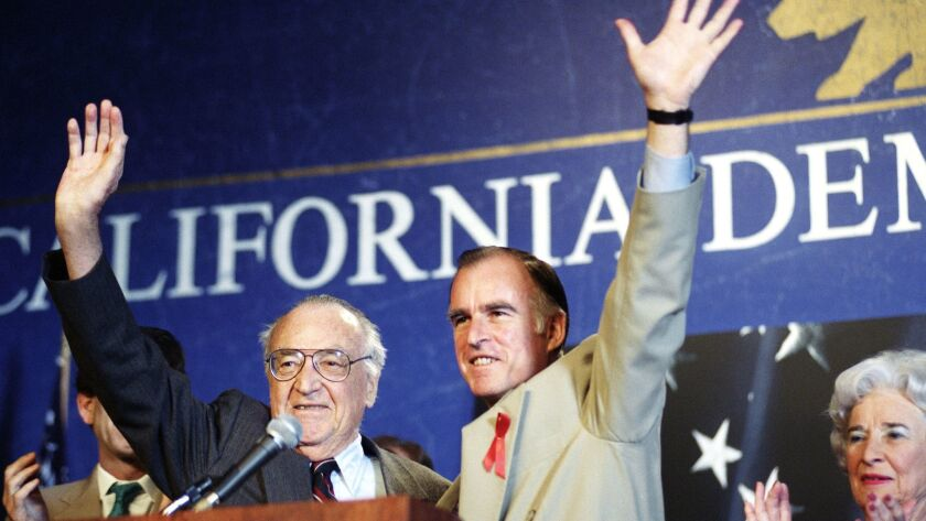 "Former Govs. Jerry Brown, right, and his father, Edmund G. ""Pat"" Brown, acknowledge the crowd at the California Democratic Party's convention in Los Angeles on April 11, 1992. Pat Brown was governor from 1959 to 1967. Jerry Brown served his first stint from 1975 to 1983."