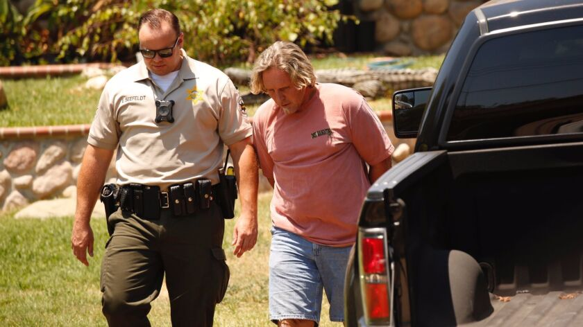Ventura County sheriff's deputies arrest Todd Kates as authorities collect American alligators and a number of snakes, some venomous, at a Thousand Oaks home.