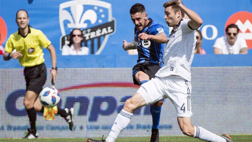 Galaxy's Dave Romney, right, challenges Montreal's Alejandro Silva during a game on May 21.