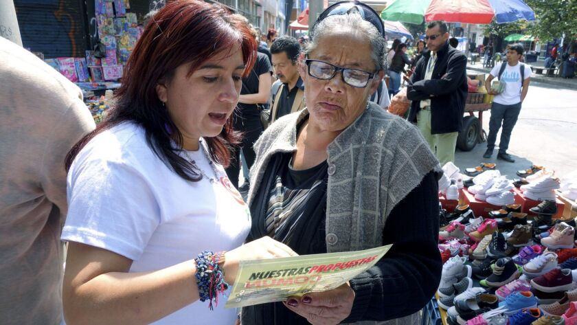 FARC congressional candidate Isabela Sanroque, left, talks with street vendor Rosalba Ayala during her walk through of the 20th of July barrio in south Bogota.