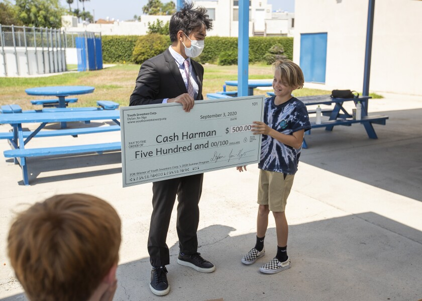 Dylan Jin-Ngo presents a check for $500 to Cash Harman at the Boys & Girls Clubs of Huntington Valley.