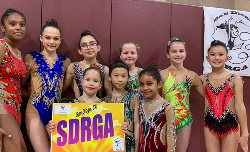 Level 9 and level 5 gymnasts of San Diego Rhythmic Gymnastics Academy: Back row: Siona Rahate, Ariana Kogan, Kayla Keller, Abigail Leychkis, Abigail Laur, Adiya Stamkulova; Front row: Alice Funtikov, Cyra Su, Tiana Ocasio