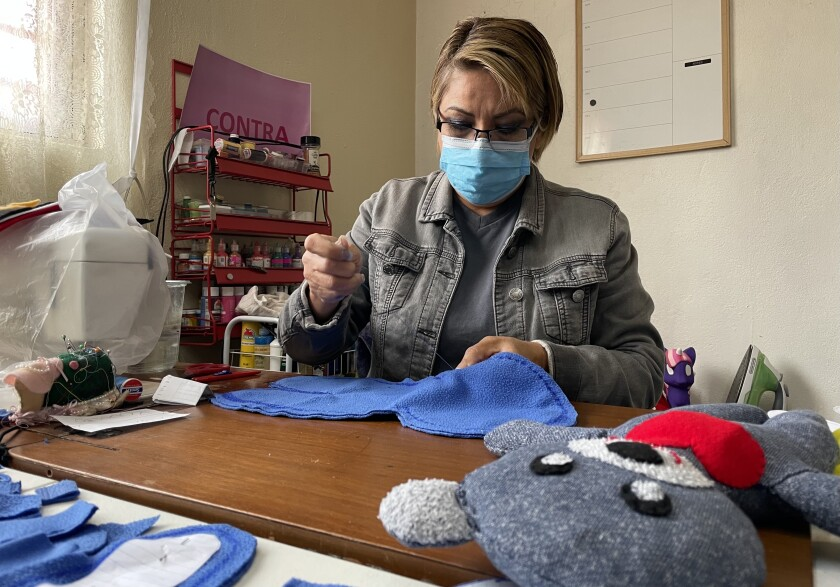 Nurse Esther Madrigal makes a teddy bear at her home in Tijuana to give