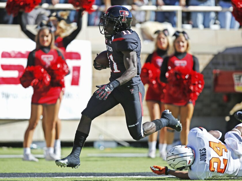 Texas Tech wide receiver Jakeem Grant (11) avoids a tackle by Oklahoma State cornerback Miketavius Jones (24) and scores in the first quarter of an NCAA college football game in Lubbock, Texas, Saturday, Oct. 31, 2015. (AP Photo/Sue Ogrocki)