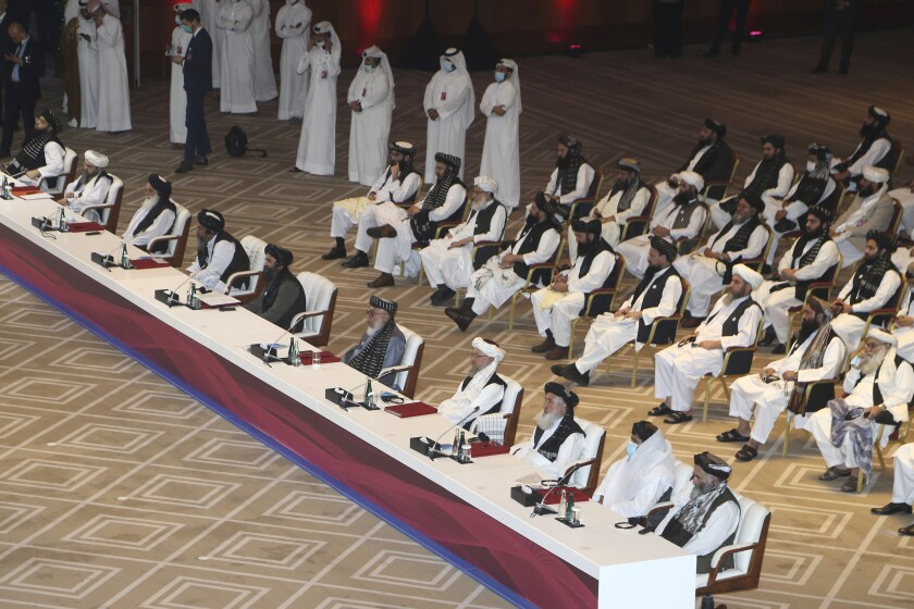 Delegates from Afghanistan sit at a long table and rows of chairs behind it in a carpeted ballroom
