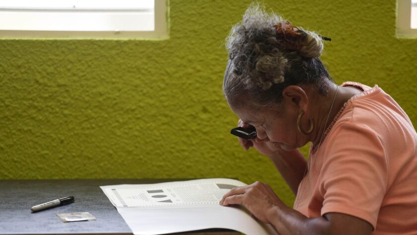 Marla Quinones examines her ballot with a magnifying glass before voting in Puerto Rico's fifth refe