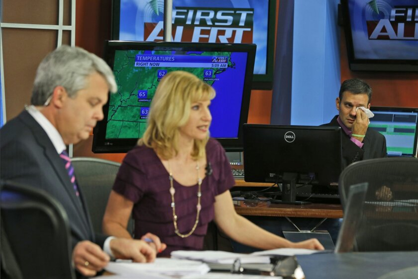 WDBJ-TV7 meteorologist Leo Hirsbrunner, right, wipes his eyes during the early morning newscast as anchors Kimberly McBroom, center, and guest anchor Steve Grant deliver the news at the station in Roanoke, Va., Thursday, Aug. 27, 2015. Reporter Alison Parker and cameraman Adam Ward were killed during a live broadcast Wednesday, while on assignment in Moneta. (AP Photo/Steve Helber)