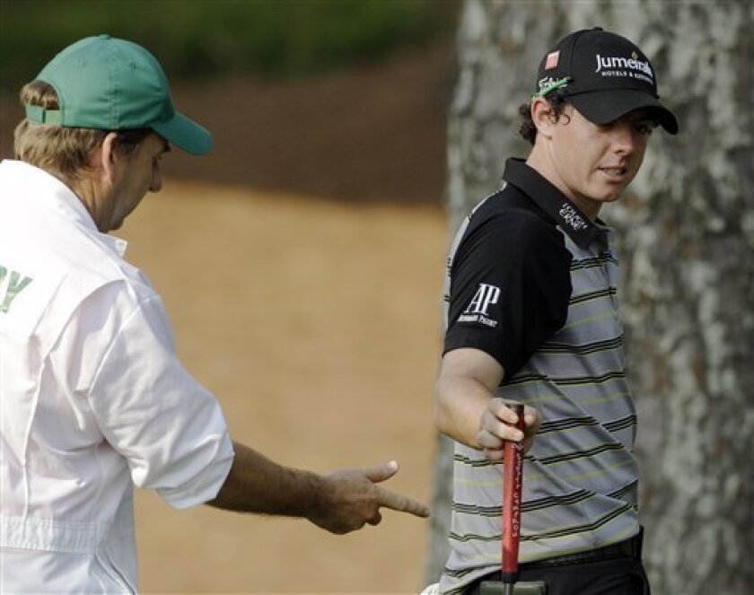 Rory McIlroy of Northern Ireland hands his putter to his caddie J.P. Fitzgerald after a triple bogey on the 10th hole during the final round of the Masters golf tournament Sunday, April 10, 2011, in Augusta, Ga. (AP Photo/Chris O'Meara)