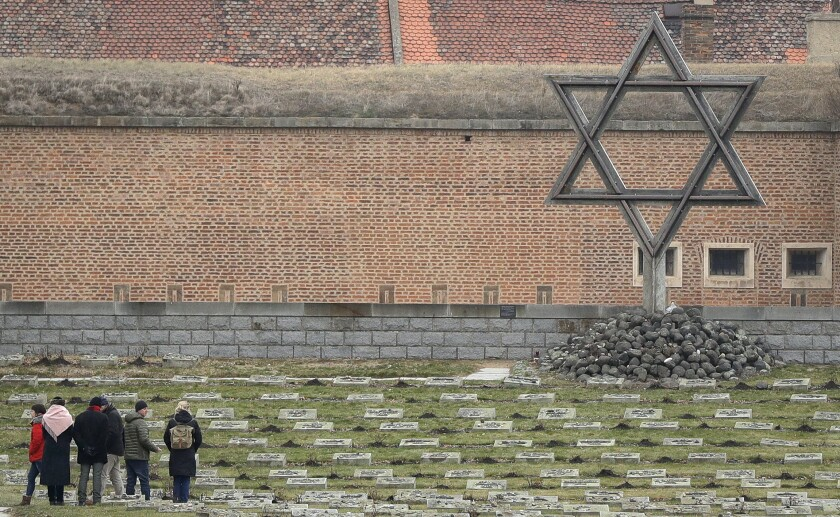 In this Thursday Jan. 24, 2019 file photo visitors walk through the cemetery of the former Nazi concentration camp in Terezin, Czech Republic. The Jewish community in the Czech Republic says there was an increase in the number of anti-Semitic incidents in the country last year. In a report Wednesday June 3, 2020. The Federation of the Jewish Communities said there were 347 anti-Semitic attacks in 2018, up by 221 from 2015 when the last equivalent report was published. (AP Photo/Petr David Josek, file)