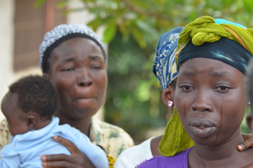 A woman cries over the death of her husband, a victim of the Ebola virus in Monrovia, Liberia.
