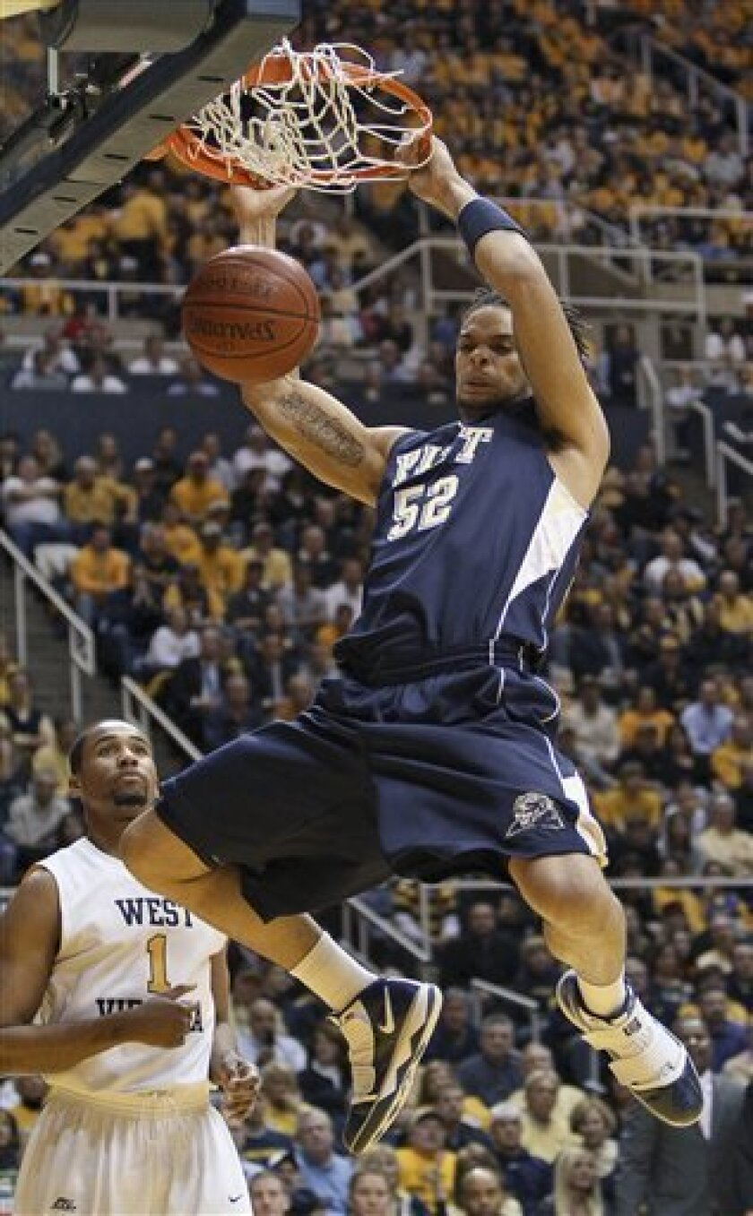 Pittsburgh's Gary McGhee (52) dunks in front of West Virginia's Da'Sean Butler, left, in the first half of an NCAA college basketball game in Morgantown, W.Va., on Wednesday, Feb. 3, 2010. (AP Photo/David Smith)