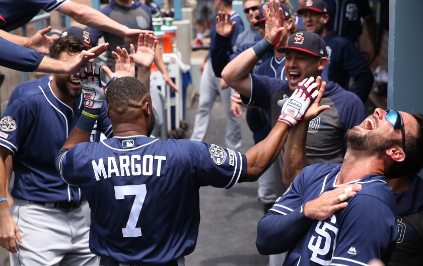LOS ANGELES, CALIFORNIA - JULY 07: Greg Garcia #5 of the San Diego Padres (R) laughs in celebration as teammate Manuel Margot #7 is congratulated by teammates after Margot hit a solo home run during the second inning of the MLB game at Dodger Stadium on July 07, 2019 in Los Angeles, California. (Photo by Victor Decolongon/Getty Images) ** OUTS - ELSENT, FPG, CM - OUTS * NM, PH, VA if sourced by CT, LA or MoD **