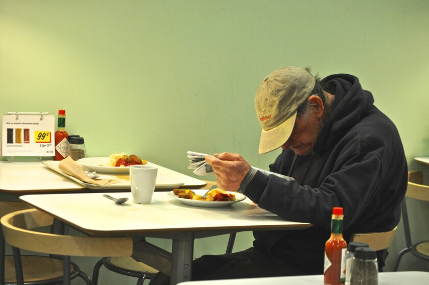 A diner reads his paper and has breakfast at Ikea's free breakfast Monday in Burbank.