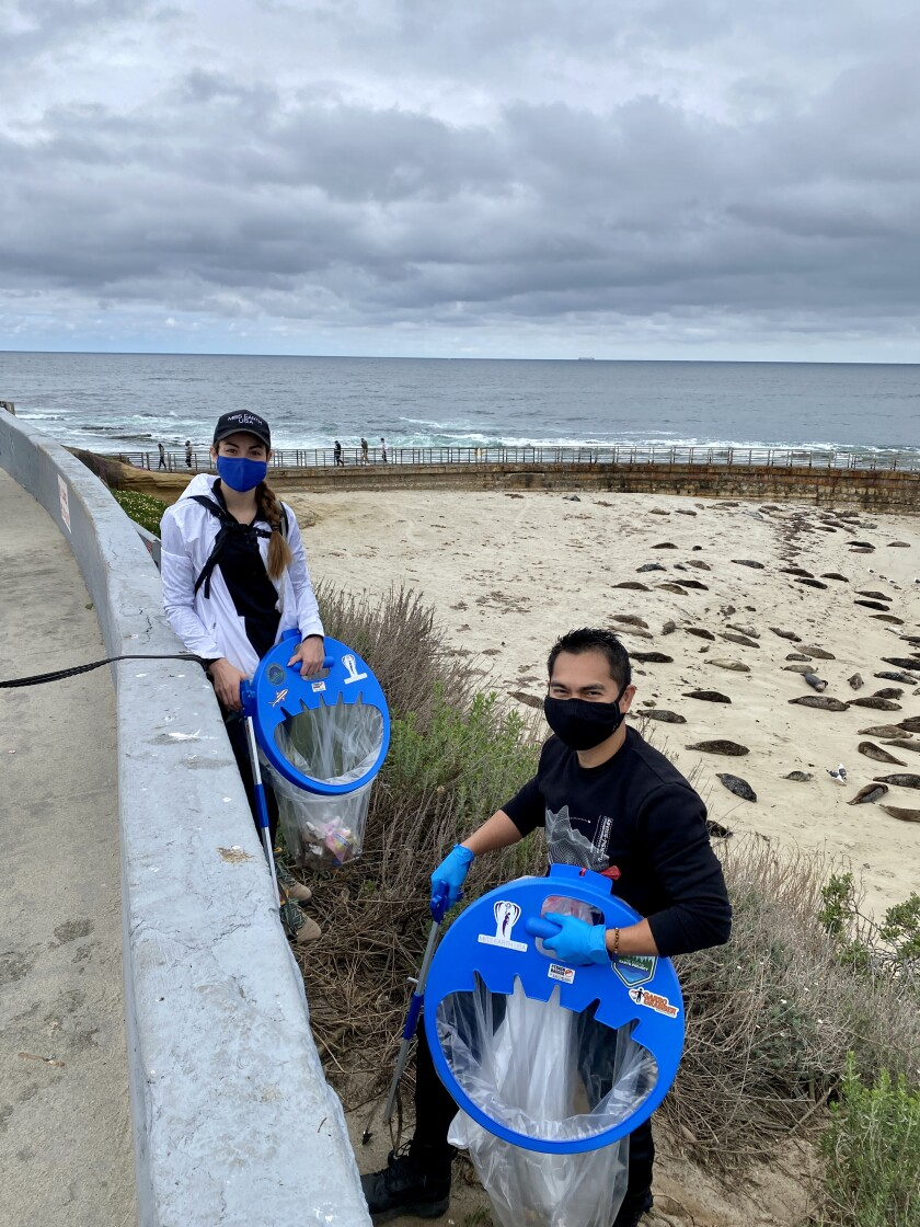 Marisa Butler and J.P. Rosal aid the Seal Society's Earth Day effort to rid the Children's Pool beach of litter.