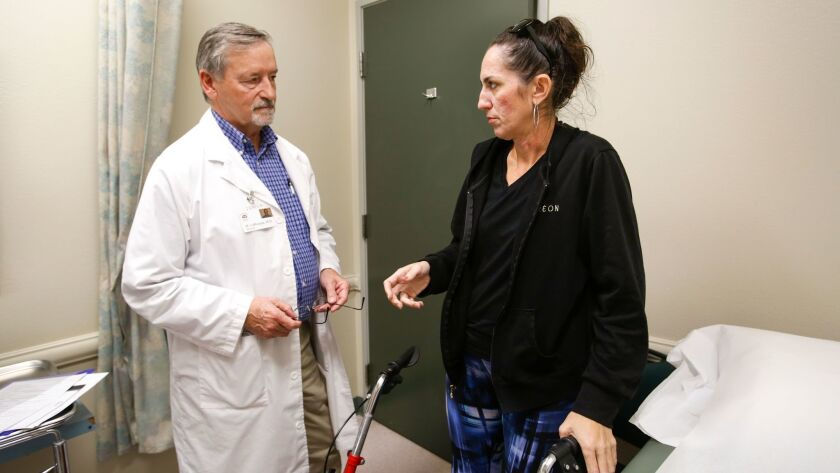 Dr. Michael LaRocque, left, talks with patient Leeann McCraw at Vista Community Clinic on Dec. 1, 2016.