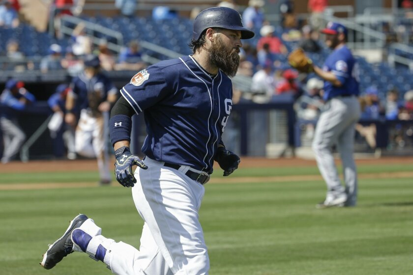 San Diego Padres' Derek Norris runs past Texas Rangers' pitcher Colby Lewis, right, after hitting a two-run home run in the first inning of a spring training baseball game, Tuesday, March 22, 2016, in Peoria, Ariz. (AP Photo/Darron Cummings)
