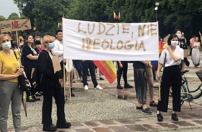 "Opponents of Polish President Andrzej Duda display a sign that reads ""People, not Ideology,"" during a protest."