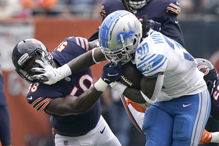 Detroit Lions running back Jamaal Williams stiff arms Chicago Bears inside linebacker Roquan Smith during the first half of an NFL football game Sunday, Oct. 3, 2021, in Chicago. (AP Photo/Nam Y. Huh)