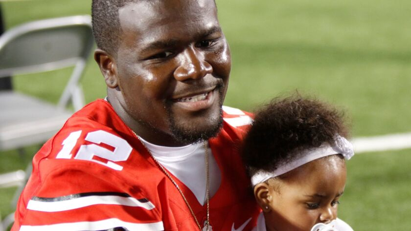 Cardale Jones speaks to reporters while holding his daughter Chloe during Ohio State's football media day Aug. 16, 2015.
