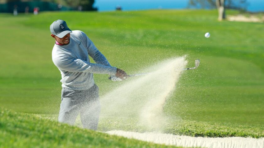 Tiger Woods hits out of the sand on the 17th hole of the north course of the Torrey Pines Golf Course during the second round of the Farmers Insurance Open on Friday, Jan. 27, 2017.