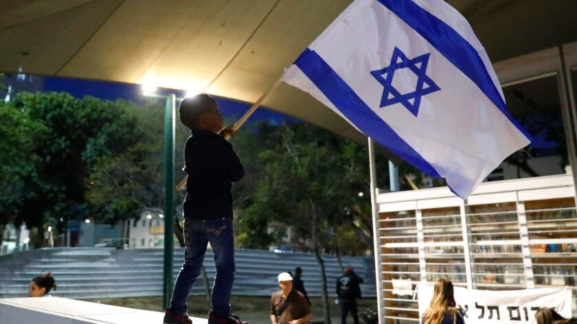 A boy waves the Israeli flag as African migrants and Israelis protest in Tel Aviv on April 9, 2018, against the government's attempt to forcibly deport African refugees and asylum seekers.