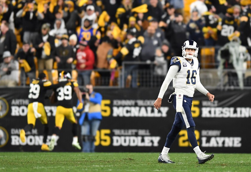 Jared Goff walks off the field after throwing an interception late.