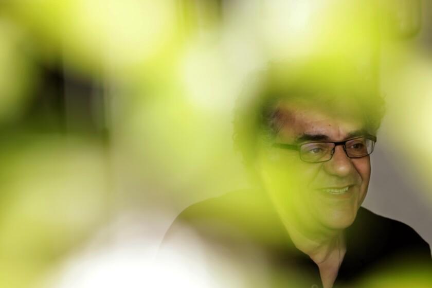 Se ve a Rodrigo García sonriendo a través del follaje