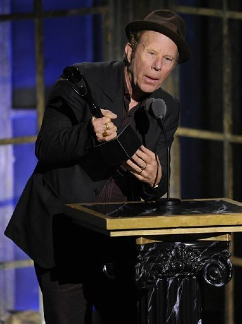 Inductee Tom Waits accepts his trophy at the Rock and Roll Hall of Fame induction ceremony, Monday, March 14, 2011, in New York.  (AP Photo/Evan Agostini)
