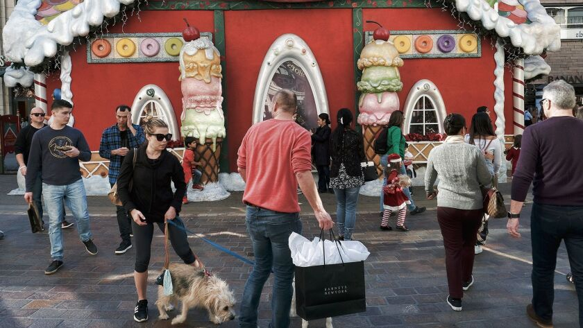 Holiday shoppers walk past Santa's Workshop for some last-minute gifts at the Grove.