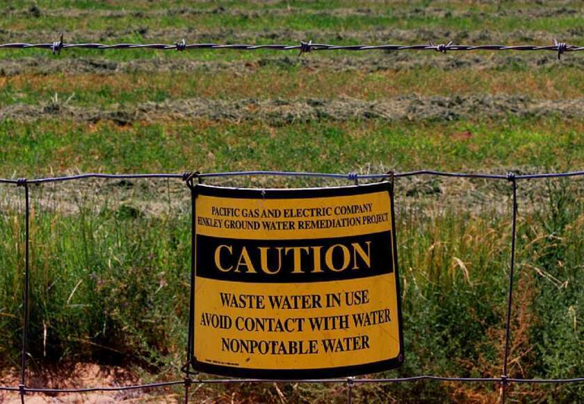 Caution signs hang on a fence surrounding a Hinkley, Calif., farm that uses irrigation water polluted with chromium, a carcinogen. California health officials are adopting the nation's first-ever drinking water standard for hexavalent chromium, which is found in water supplies across the state.
