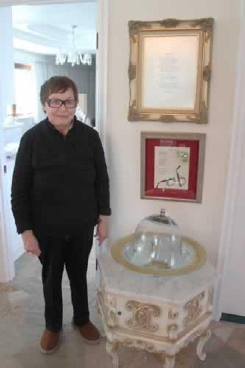 """Frieda L. Levinsky stands next to several of her framed poems. She is the author of the 2007 collection of verse, """"Enlightened Ambiance."""""""