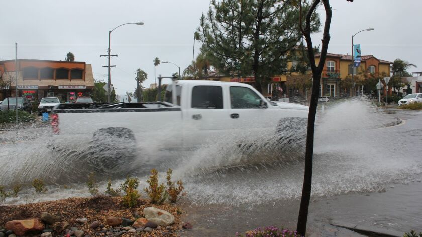 A truck splashes as it drives into the La Jolla Boulevard and Forward Street roundabout in Bird Rock, Feb. 27.