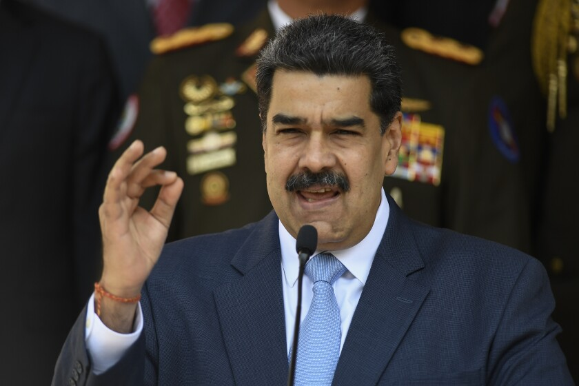 Venezuelan President Nicolás Maduro speaks into a microphone at a news conference