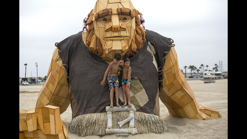 """Luke Grove, 10, and his brother Brycen, 8, climb on a Giant from the game """"Clash of Clans"""" on Aug. 25 at Huntington State Beach."""