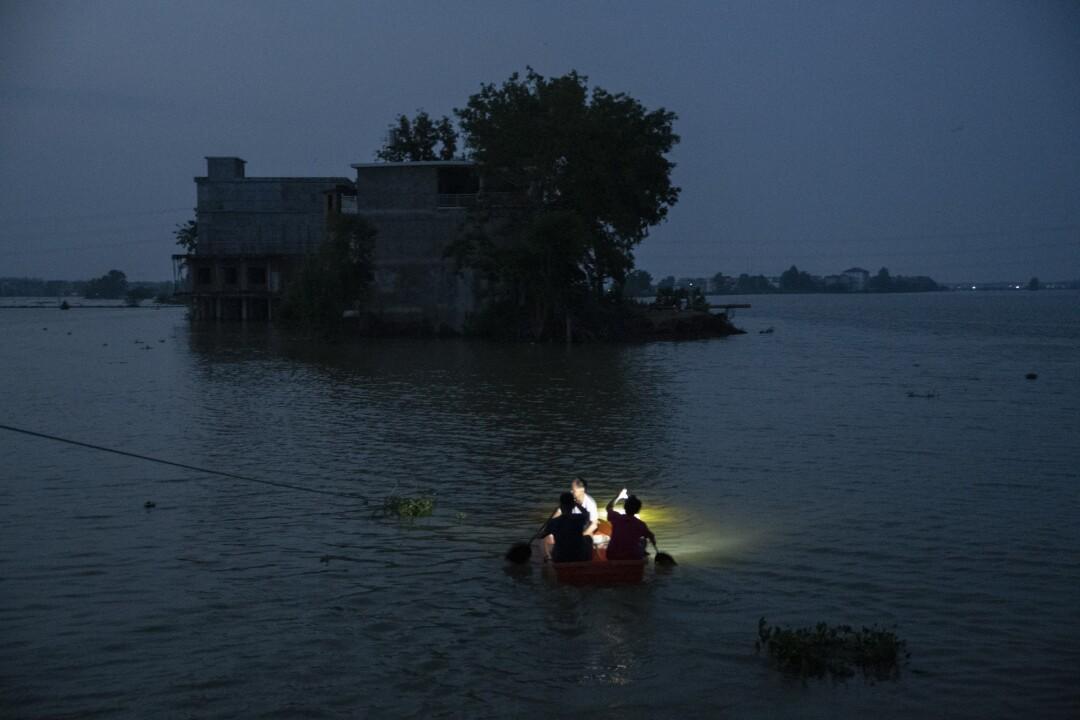 Villagers row a boat through the broken embankment.