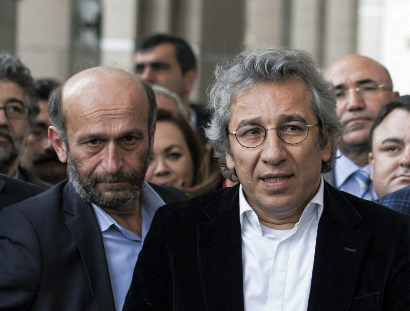 In this Thursday, Nov. 26, 2015 photo, Can Dundar, right, the editor-in-chief of opposition newspaper Cumhuriyet, and Erdem Gul, left, the paper's Ankara representative, speak to the media outside a courthouse in Istanbul, Turkey. In new blow to media freedoms in Turkey, a court on Thursday ordered the two prominent opposition journalists jailed pending trial over charges of willingly aiding an armed group and of espionage for revealing state secrets for their reports on alleged arms smuggling to Syria. In May, the Cumhuriyet paper published what it said were images of Turkish trucks carrying ammunition to Syrian militants. (Vedat Arik/Cumhuriyet via AP) TURKEY OUT