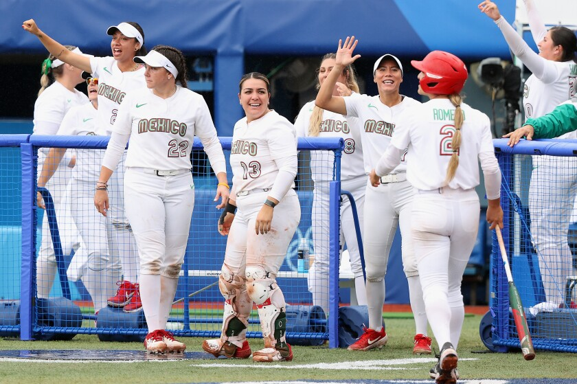Team Mexico players including Sashel Palacios (13) react after an RBI single during the women's bronze medal softball game.