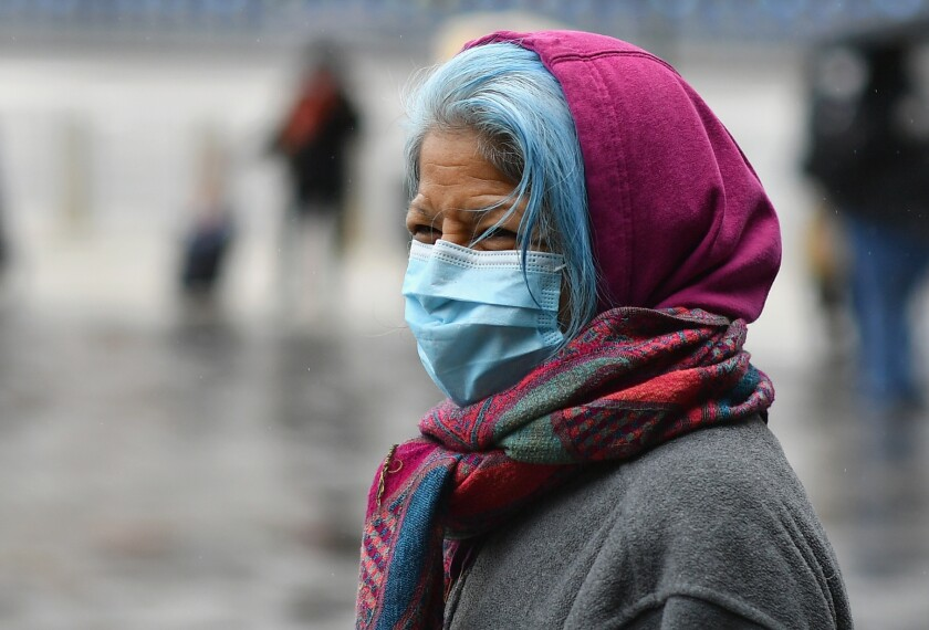 A woman waits in line in Brooklyn for a mobile food pantry.