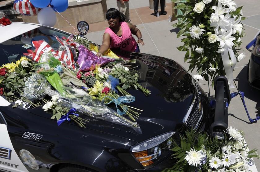 Cynthia Ware deposita flores en un monumento improvisado en las oficinas generales de la policía de Dallas el viernes 8 de julio de 2016, en Dallas, tras la muerte de cinco agentes por un francotirador. (AP Foto/Eric Gay)